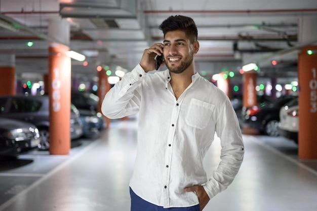 Fiducioso giovane bell'uomo che cammina lungo il parcheggio mentre parla al telefono dopo aver p...