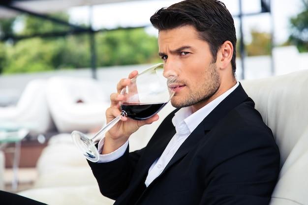 Fiducioso giovane uomo che beve vino nel ristorante