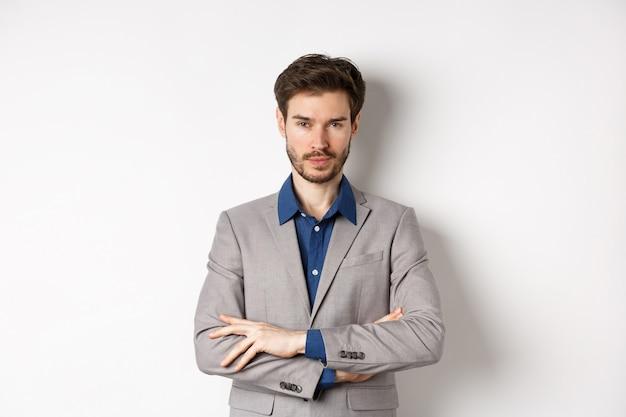 Fiducioso giovane uomo che sembra professionista, braccia incrociate sul petto in tailleur, in piedi su sfondo bianco.
