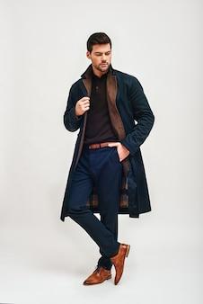 Fiducioso giovane elegante uomo dai capelli scuri in piedi tenendo una mano nella tasca dei pantaloni e guardando