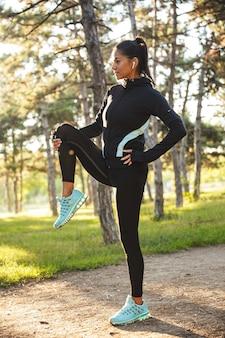 Fiduciosa giovane donna sportiva in fase di riscaldamento prima di fare jogging al parco, ascoltando musica con auricolari wireless