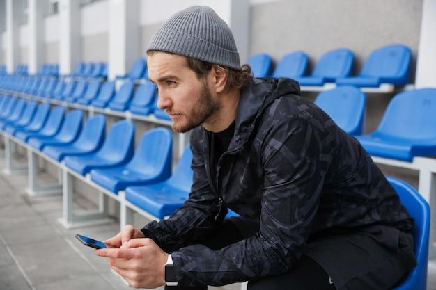 Fiducioso giovane sportivo seduto sui sedili della tribuna allo stadio, utilizzando il telefono cellulare
