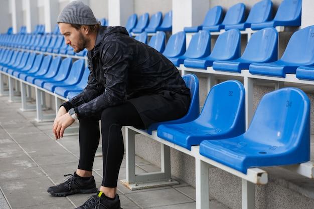 Fiducioso giovane sportivo seduto sui sedili della tribuna allo stadio
