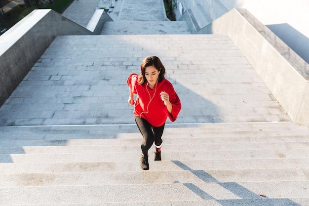 Fiduciosa giovane sportiva in esecuzione su per le scale all'aperto