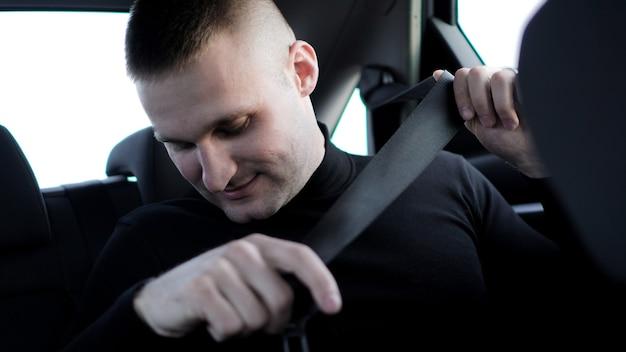 Fiducioso giovane uomo d'affari alla moda nella sua auto allacciare la cintura di sicurezza