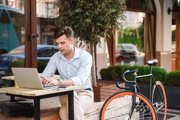 Fiducioso giovane uomo elegante che lavora al computer portatile