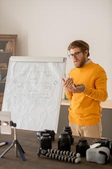 Fiducioso giovane insegnante in abbigliamento casual in piedi dalla lavagna davanti alla fotocamera dello smartphone e spiegando l'argomento al pubblico online