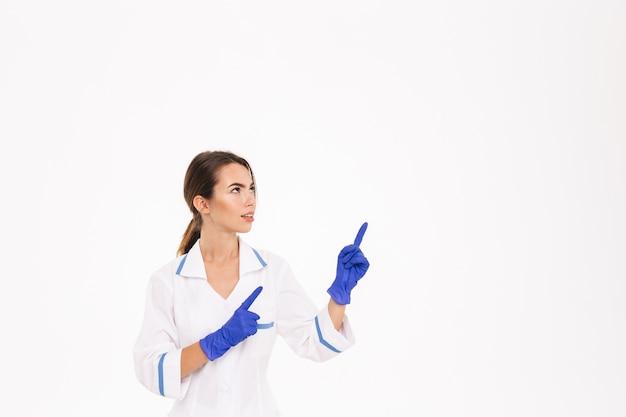 Fiducioso giovane donna medico indossando guanti di gomma e uniformi in piedi isolato sopra il muro bianco, indicando lontano