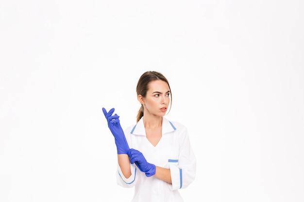 Fiducioso giovane donna medico indossando guanti di gomma e uniformi in piedi isolato sopra il muro bianco