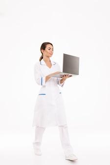 Fiducioso giovane donna medico indossa uniforme in piedi isolato sul muro bianco, utilizzando il computer portatile
