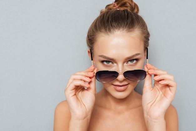 Fiduciosa giovane donna che guarda la fotocamera attraverso occhiali da sole isolati su uno sfondo grigio