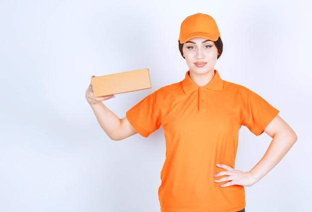 Fiduciosa giovane donna in unishape arancione con pacchetto su parete bianca