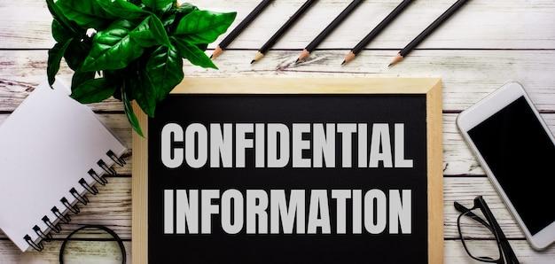 Informazioni riservate sono scritte in bianco su una lavagna nera accanto a un telefono, un blocco note, occhiali, matite e una pianta verde.