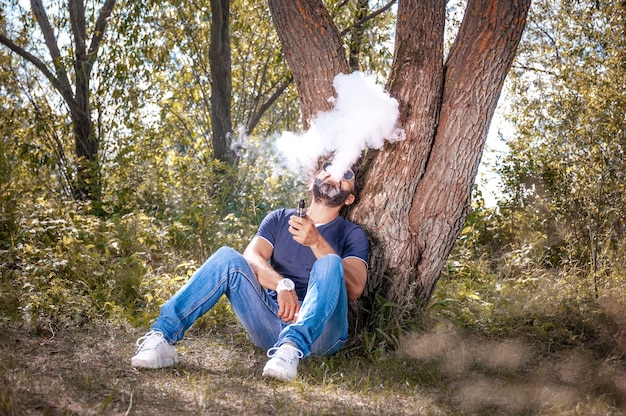 L'uomo fiducioso sta riposando fuori e svapando e scaricando vapore da un dispositivo elettronico per il fumo. t