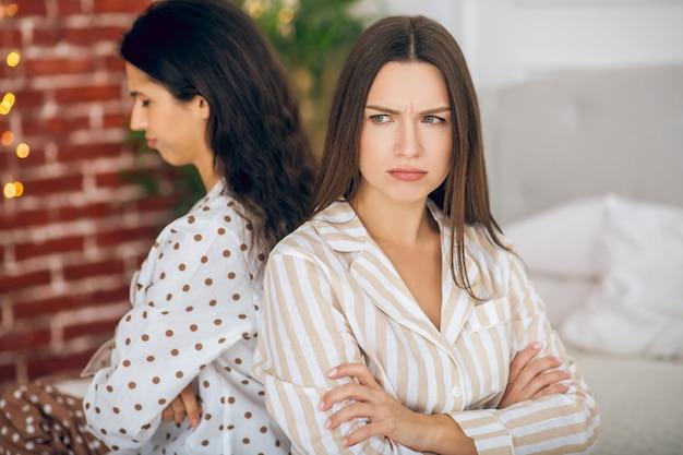 Conflitto. due giovani ragazze in pigiama seduti schiena contro schiena su un letto