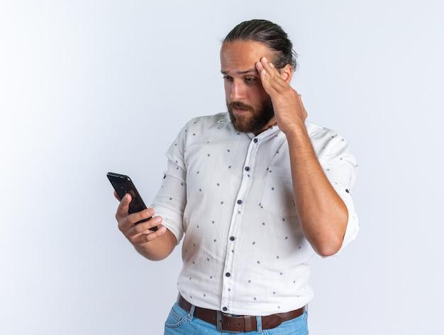 Bell'uomo adulto confuso con gli occhiali che tiene la mano sulla testa tenendo e guardando il telefono cellulare isolato sul muro bianco