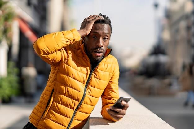 Uomo africano confuso con il telefono cellulare che si lamenta dell'errore che si siede in una città