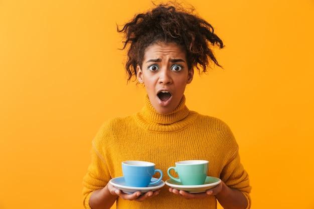 Maglione da portare della donna africana confusa che tiene le tazze sui piattini isolati