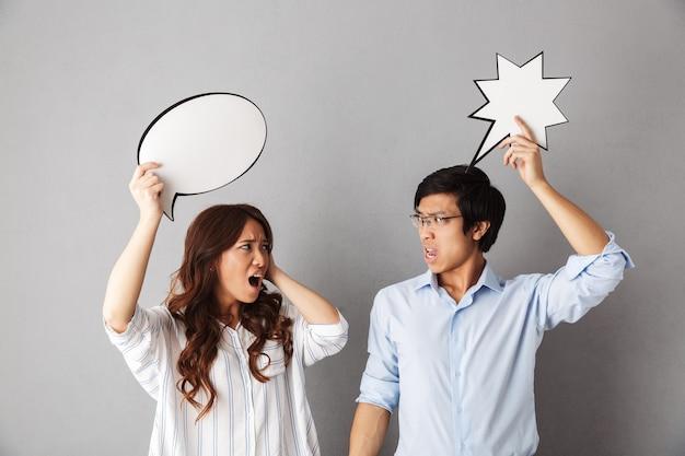 Confuso coppia asiatica in piedi isolato, tenendo vuoto discorso bolla, avendo un argomento