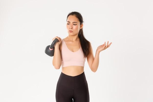 Ragazza asiatica confusa di forma fisica in activewear che sembra perplessa, sollevamento kettlebell, diventando forte con allenamento e dieta sana, in piedi sfondo bianco.
