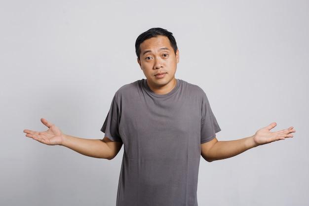 Uomo asiatico confuso da una domanda difficile o nessuna idea con un gesto impotente