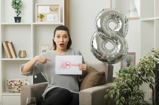 Bella ragazza confusa nel giorno delle donne felici che tiene e indica il biglietto di auguri seduto sulla poltrona in soggiorno
