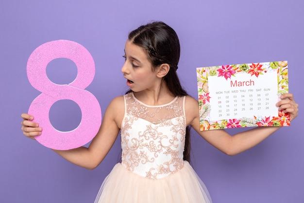 Bella bambina confusa il giorno della donna felice che tiene il numero otto con il calendario isolato sulla parete blu