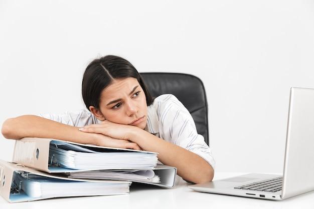 Donna di affari castana confusa che si siede al tavolo con cartelle di carta in ufficio e lavora al computer portatile isolato sopra il muro bianco
