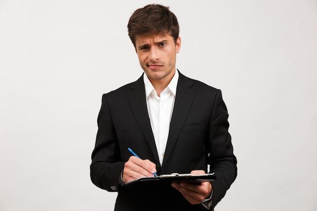 Confuso uomo d'affari in piedi isolato tenendo appunti.