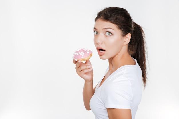 Giovane donna di dieta confusa che tiene gustosa ciambella isolata sopra il muro bianco