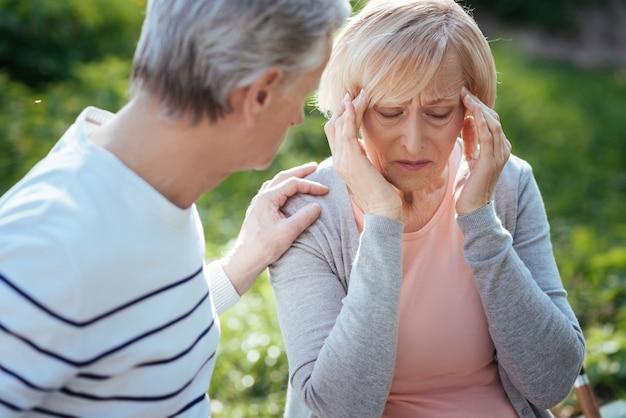 Donna anziana confusa e delusa che si tocca la testa e sente dolore mentre il marito anziano si preoccupa per la sua salute e si siede sulla panchina all'aperto