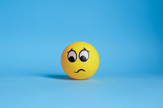 Emoticon confuso isolato su priorità bassa blu