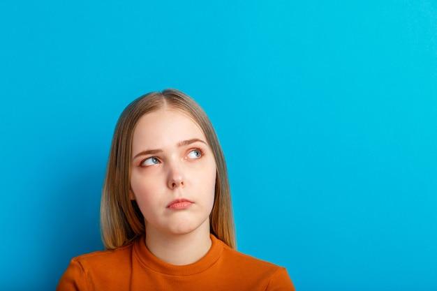 Ritratto emotivo confuso dell'adolescente dubbio con la domanda che osserva in su. la giovane donna pensa