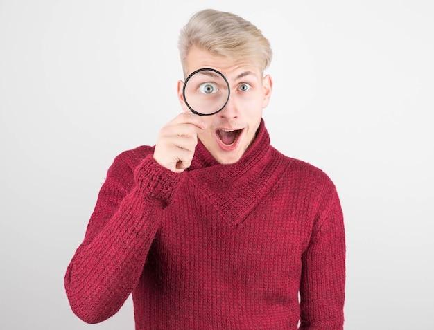 Espressione confusa di un giovane che tiene una lente d'ingrandimento nei suoi occhi. il viso curioso e bello di un giovane. in un maglione rosso