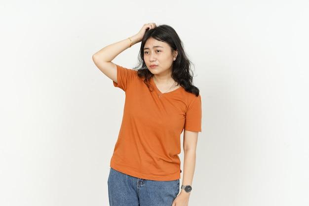 Espressione del viso confuso di una bella donna asiatica che indossa una maglietta arancione isolata su bianco