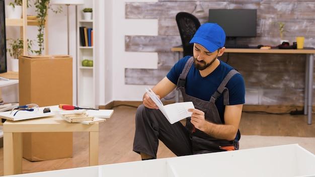 Operaio confuso dell'assemblaggio di mobili durante la lettura delle istruzioni per montare uno scaffale.