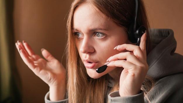 Operatore ragazza confusa con auricolare lavoro remoto da casa in un call center