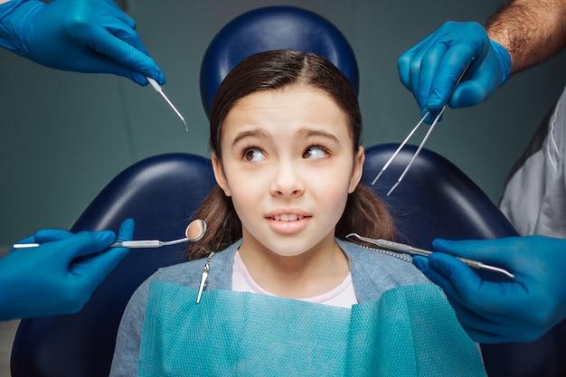 La ragazza confusa si siede nella sedia dentale nella sala. le mani dell'adulto in guanti di lattice tengono gli strumenti del dentista. li guarda. strano e spaventoso.