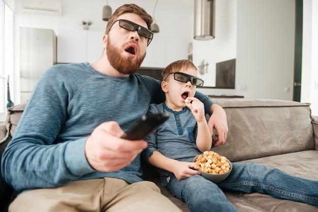 Padre felice confuso che tiene il telecomando mentre guarda la tv con il suo piccolo figlio carino usando occhiali 3d che tengono popcorn.