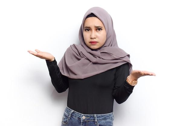 Confuso o non so gesto di giovani belle donne asiatiche musulmane vestono velo hijab