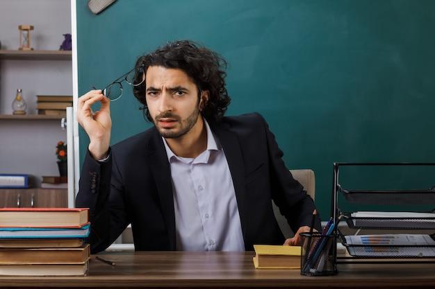 Insegnante maschio della macchina fotografica dall'aspetto confuso che tiene gli occhiali seduto al tavolo con gli strumenti della scuola in classe