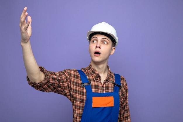 Confuso guardando lato alzando la mano giovane costruttore maschio che indossa l'uniforme