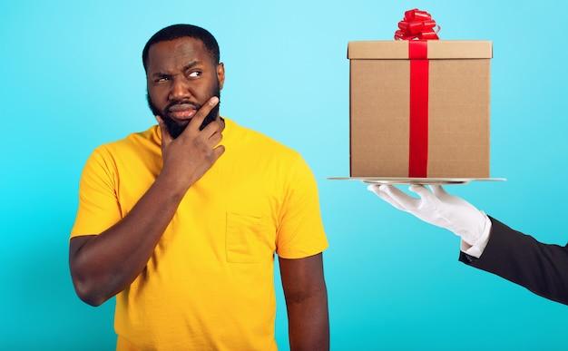 L'uomo confuso è sospettoso riguardo a un regalo. concetto di opzioni, confusione, indecisione