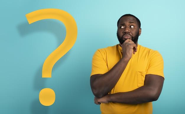 Espressione confusa e pensierosa di un ragazzo con molte domande sulla superficie color ciano