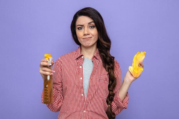 Donna pulita piuttosto caucasica confusa che tiene in mano panni per la pulizia e detergente spray