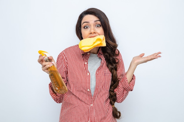 Donna delle pulizie piuttosto caucasica confusa che tiene i panni per la pulizia con i denti e tiene in mano un detergente spray