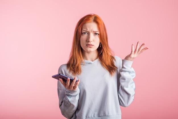 Ragazza rossa confusa con il telefono in studio su sfondo rosa