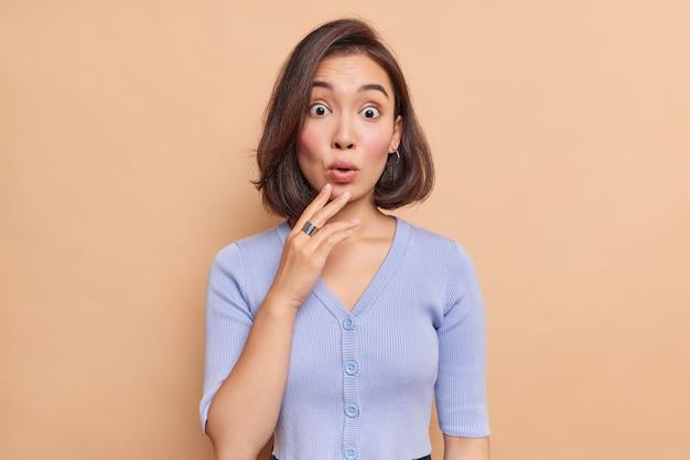 La donna asiatica bruna scioccata confusa reagisce a qualcosa con un'espressione spaventata e meravigliata indossa un maglione blu sembra sorpreso fissa il logo promozionale indossa un maglione blu isolato sul muro beige