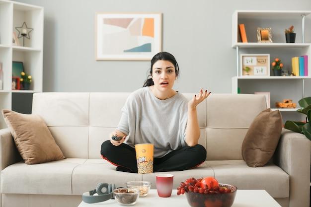 Ragazza confusa a mano allargata con secchio di popcorn che tiene il telecomando della tv, seduta sul divano dietro il tavolino da caffè nel soggiorno
