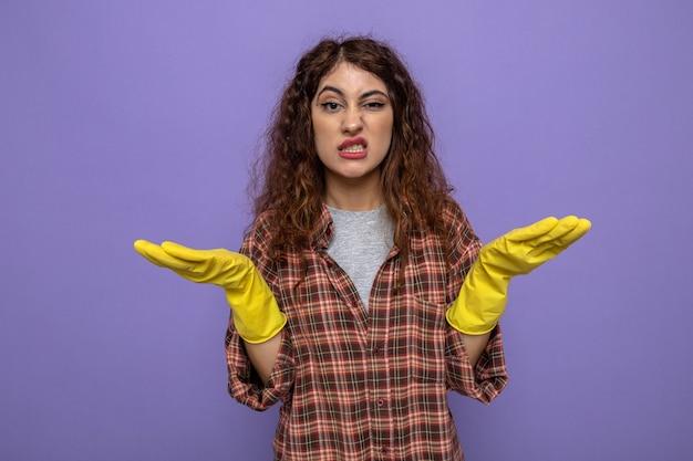 Mani allargate confuse giovane donna delle pulizie che indossa guanti